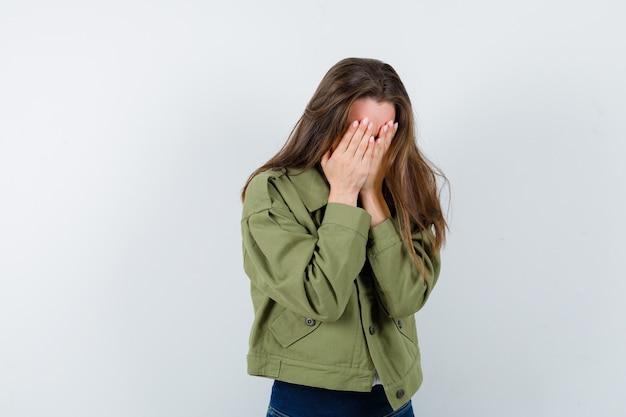 Молодая женщина закрыла лицо руками в рубашке, куртке и выглядела возбужденным, вид спереди.
