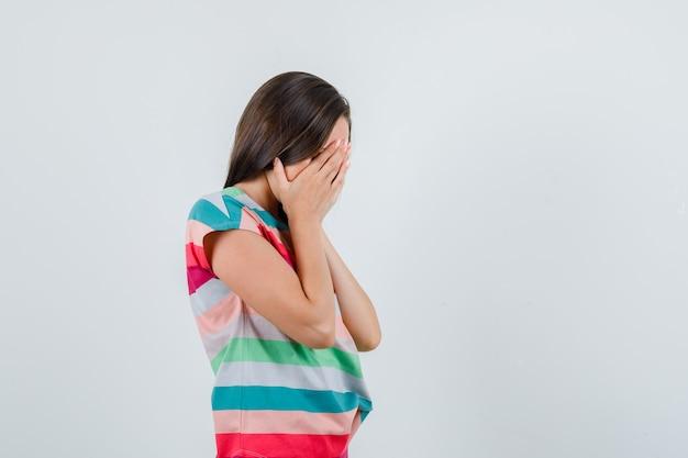 Молодая женщина закрыла лицо руками в футболке и выглядела смущенной. .