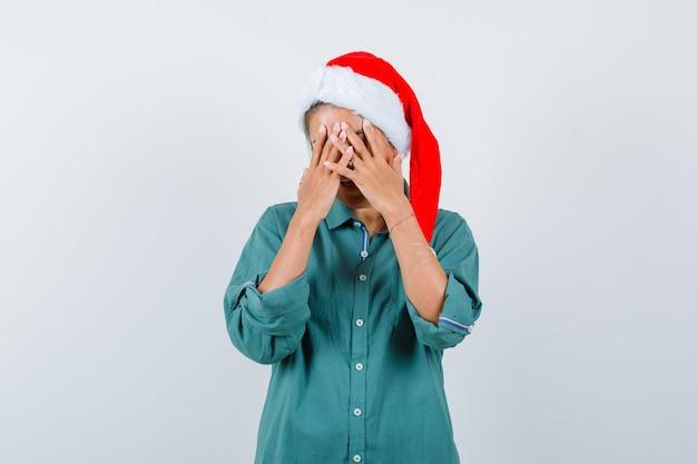 Giovane donna che copre il viso con le mani in camicia, cappello da babbo natale e sembra depressa. vista frontale.