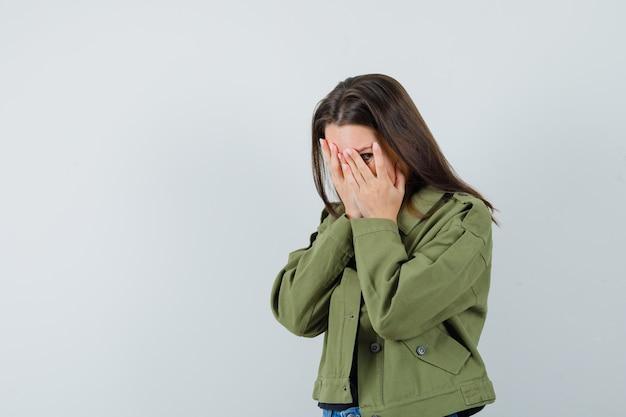 緑のジャケット、正面図で指を通して見ながら手で顔を覆う若い女性。テキスト用のスペース