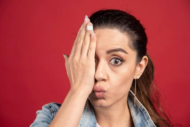 赤い背景に手で目を覆う若い女性。高品質の写真