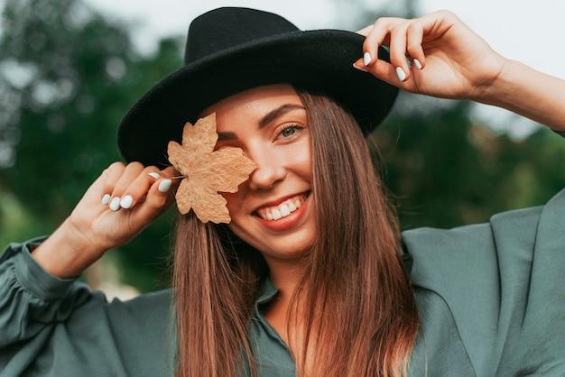 Молодая женщина закрыла глаза сухим листом