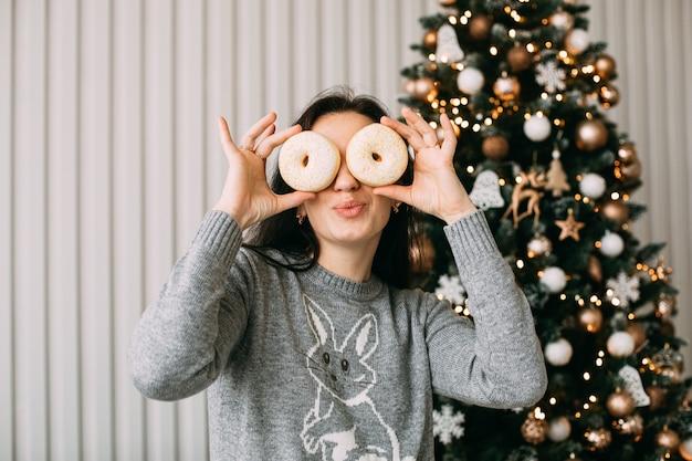 도넛으로 그녀의 눈을 덮고 젊은 여자 프리미엄 사진