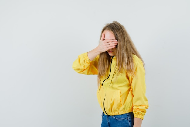 Young woman covering her eyes with hand in yellow bomber jacket and blue jean and looking shy, front view.