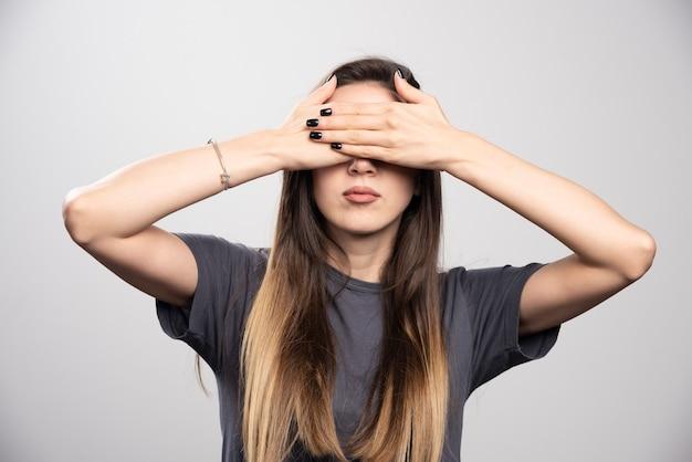 Молодая женщина закрыла глаза руками на сером фоне.