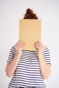 Young woman covering her face with book  shot
