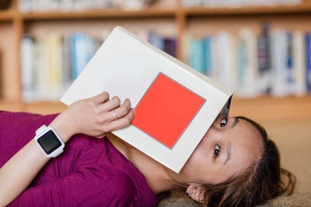 本で彼女の顔を覆っている若い女性