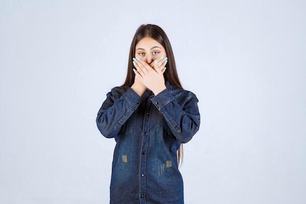 彼女の口を覆い、沈黙を保つ若い女性
