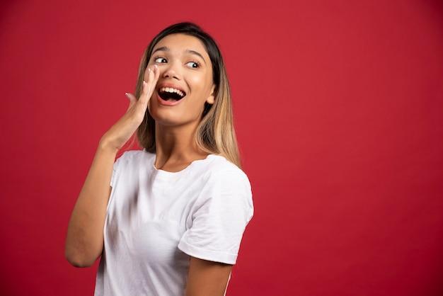 Giovane donna che copre la bocca con la mano sulla parete rossa.