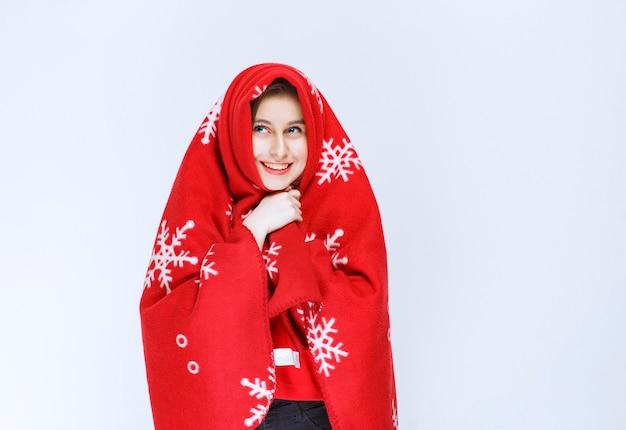 赤い暖かい毛布で身を覆っている若い女性。