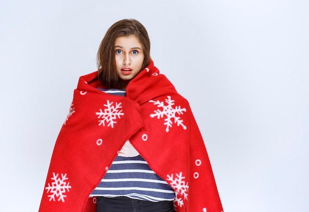 Giovane donna che copre se stessa con una calda coperta rossa e che tiene una coperta a strisce blu.