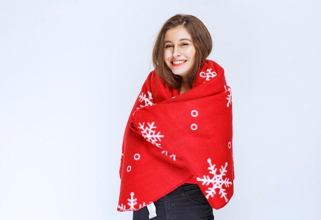 Young woman covering herself with a red warm blanket.