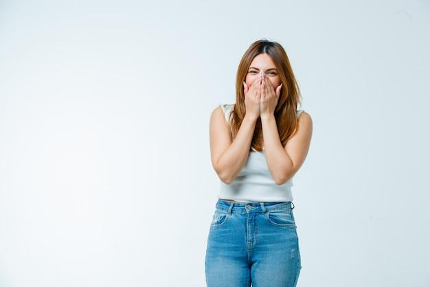 Молодая женщина, прикрывая рот и нос руками, смеясь