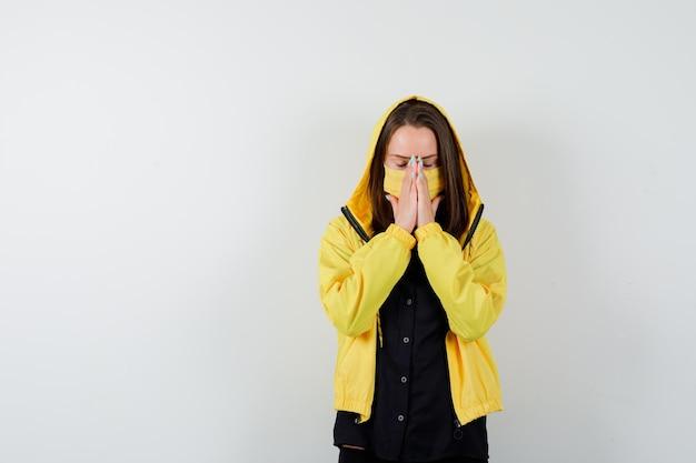 Молодая женщина, закрывающая рот и нос руками
