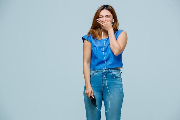Молодая женщина, закрывающая рот, улыбаясь