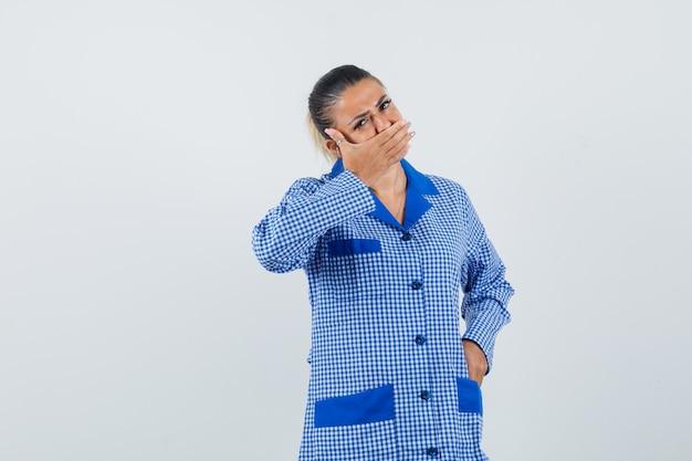 블루 깅엄 파자마 셔츠에 손으로 입을 덮고 예쁜 찾고 젊은 여자. 전면보기.