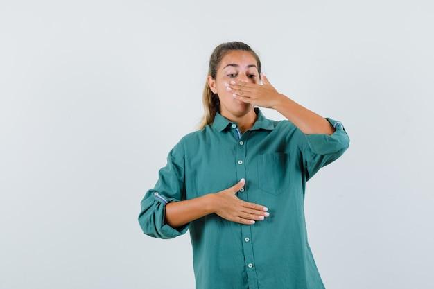 녹색 블라우스에 손으로 입을 덮고 지쳐 보이는 젊은 여자