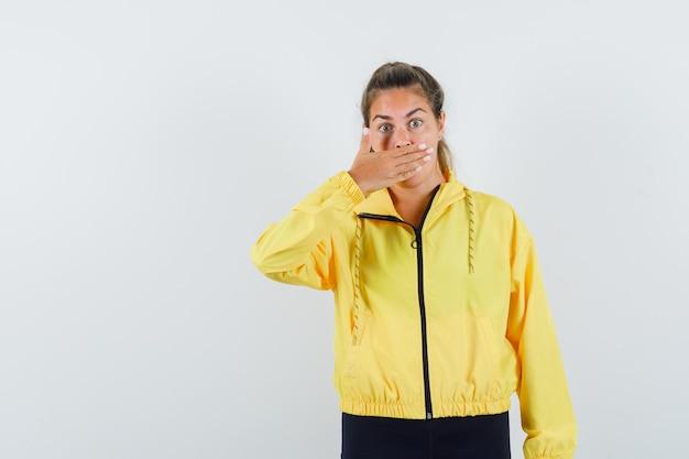 黄色のボンバージャケットと黒のズボンで手で口を覆い、驚いて見える若い女性