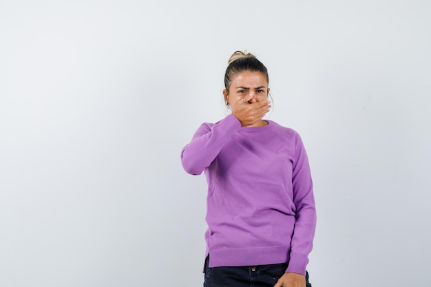 Giovane donna che copre la bocca con la mano e sembra scioccata