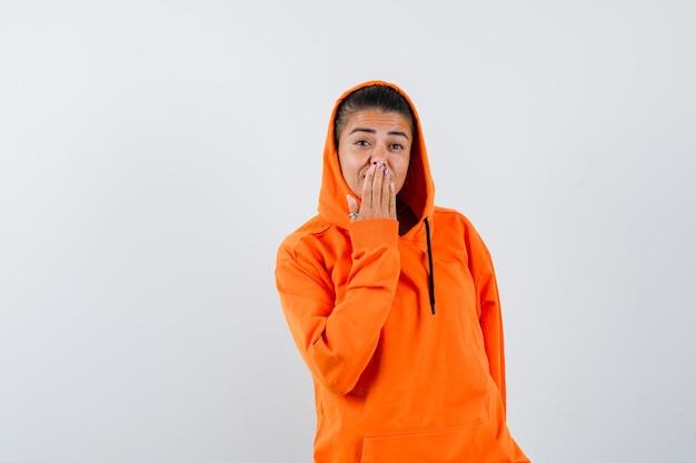 Giovane donna che copre la bocca con la mano in una felpa con cappuccio arancione e sembra felice