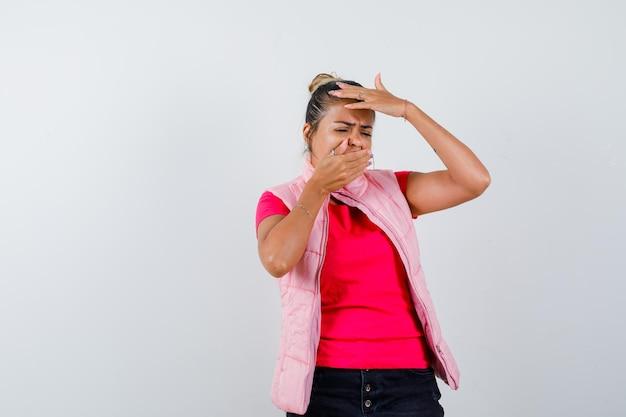 Giovane donna che copre la bocca con la mano, mette una mano sulla fronte in maglietta e giacca rosa e sembra triste looking
