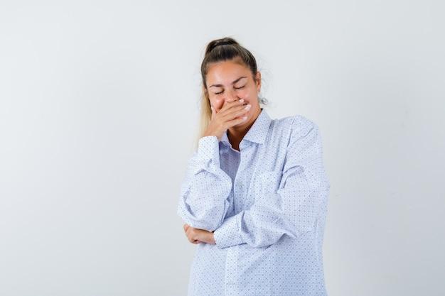 Молодая женщина прикрывает рот рукой, улыбается, держит глаза закрытыми в белой рубашке и выглядит счастливой