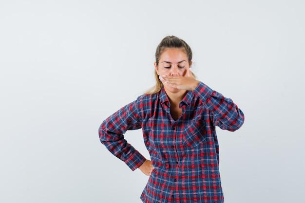 Молодая женщина прикрывает рот рукой, держа руку на животе в клетчатой рубашке и выглядит усталой