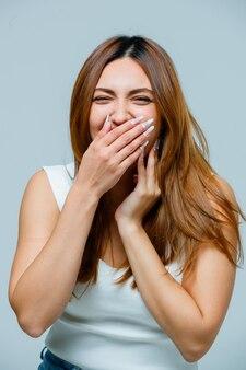 Молодая женщина, прикрывая рот рукой, смеясь