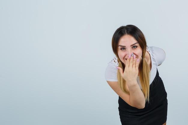 Giovane donna che copre la bocca con la mano mentre sorride