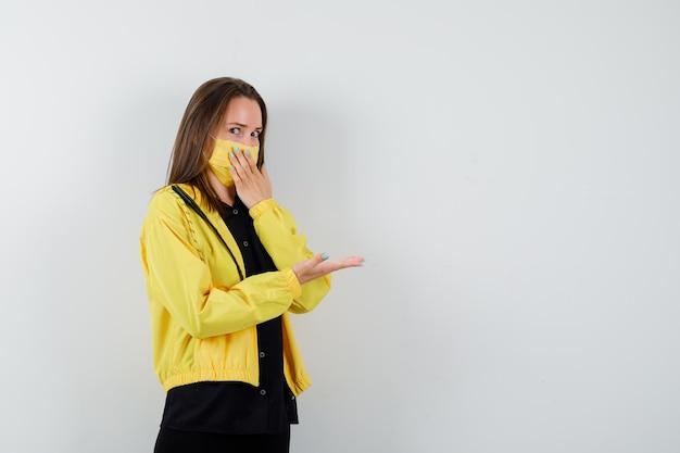 Молодая женщина, закрывающая рот рукой