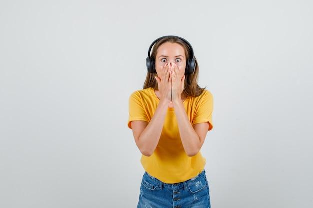 Tシャツ、ショートパンツ、ヘッドフォンで手で口を覆い、怖がって見える若い女性