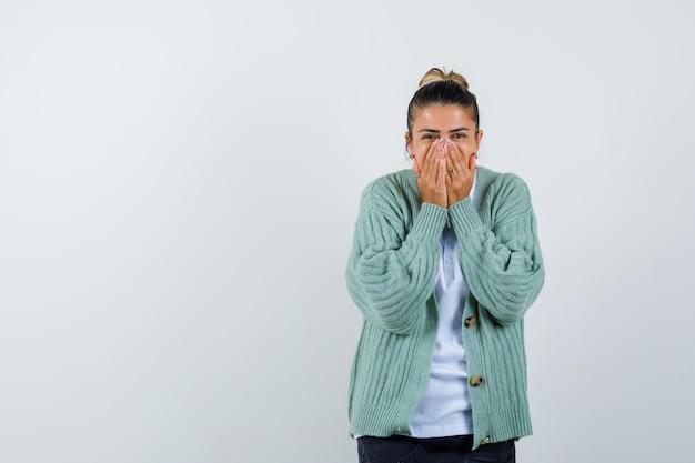 白いtシャツとミントグリーンのカーディガンで手で口を覆って驚いて見える若い女性