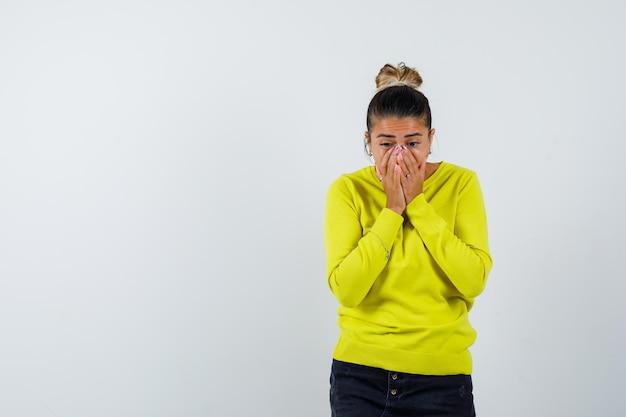 黄色いセーターと黒いズボンで手で口を覆い、驚いて見える若い女性