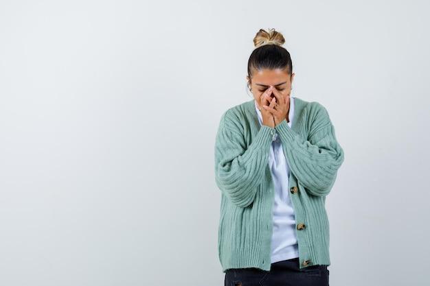 手で口を覆い、白いtシャツとミントグリーンのカーディガンで見下ろし、疲れている若い女性