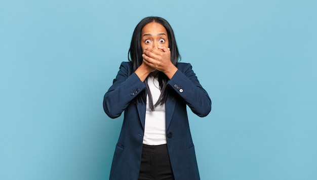Young woman covering mouth with hands with a shocked, surprised expression, keeping a secret or saying oops