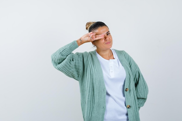 Giovane donna che copre un occhio con le dita in camicia bianca e cardigan verde menta e sembra felice