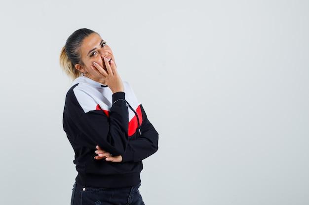 Giovane donna che copre parte del viso con le mani in maglione e jeans neri e sembra timida, vista frontale.