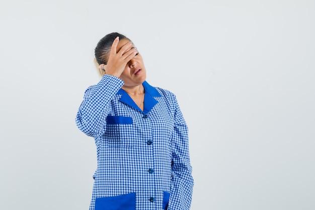 青いギンガムチェックのパジャマシャツで顔の一部を手で覆い、疲れている若い女性。正面図。