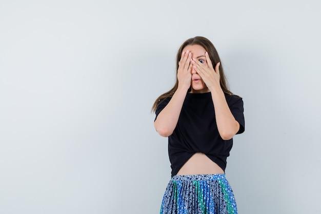 손으로 얼굴의 일부를 덮고 검은 색 티셔츠와 파란색 치마에 손가락을 통해보고 매력적인 젊은 여자