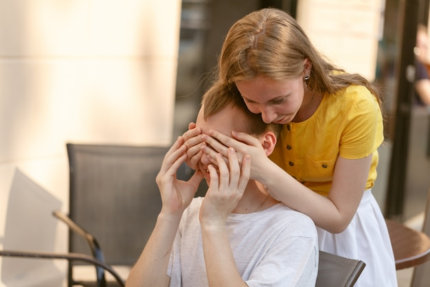 Young woman covering a young man's eyes and smiling