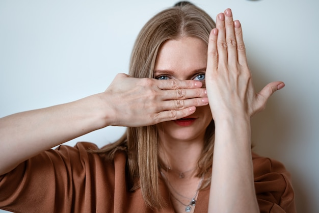 Young woman covers her face with her hands on the background of a light wall