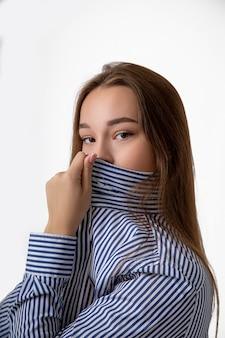 若い女性は、細菌やcovid-19ウイルスを恐れて、マスクの代わりにシャツで鼻と口を覆っています。