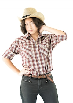 Young woman in a cowboy hat and plaid shirt with hand on her hat