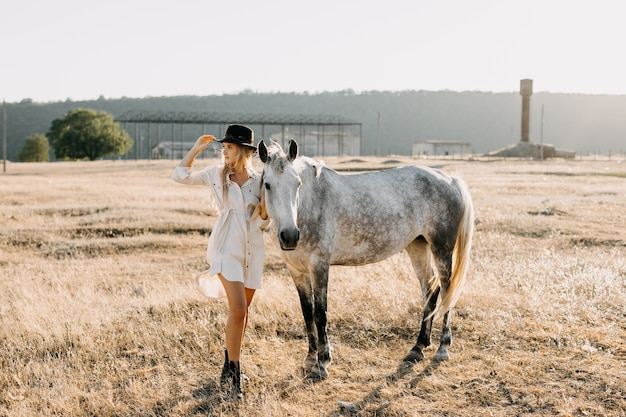 Young woman cowboy with a horse standing at a farm