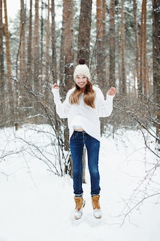 Young woman in cozy clothes having fun in winter