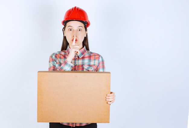 A young woman in crash helmet doing silent sign and holding paper box.