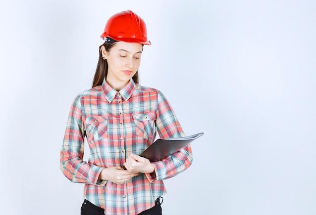Una giovane donna in casco che tiene cartella nera.