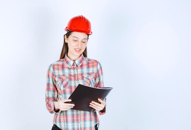 Una giovane donna in casco che prende appunti nella cartella nera.