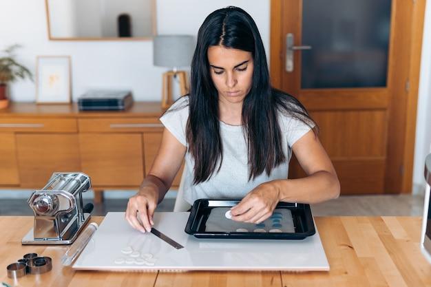粘土と道具を使って自宅でカラフルな手作りのジュエリーを作成する若い女性。