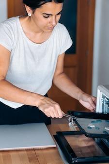 Молодая женщина создает украшения ручной работы с помощью духовки и работает из дома.